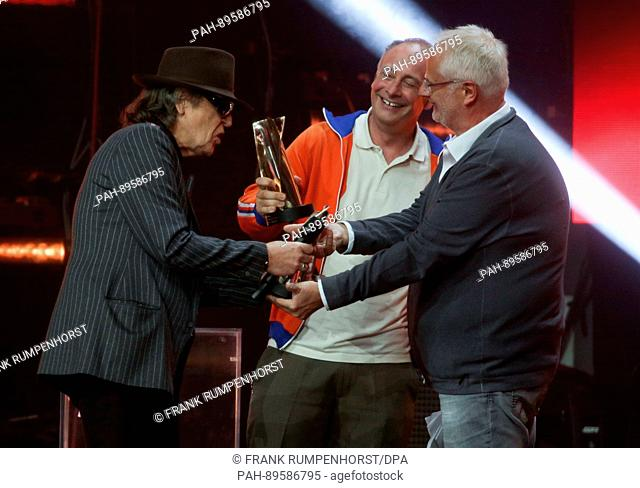 """Comedian Alfons (M) hands the LEA Prize for the best stadium tour to singer Udo Lindenberg (L) and concert organiser Roland """"""""Balou""""""""Temme (R) at the Festhalle..."""