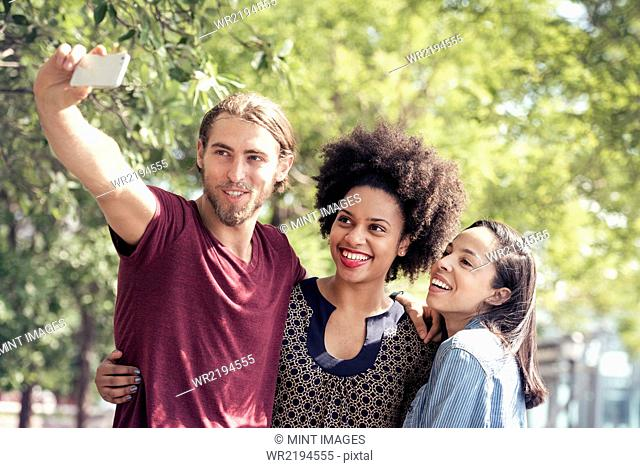 Three people, a man and two women, taking selfies in a city park