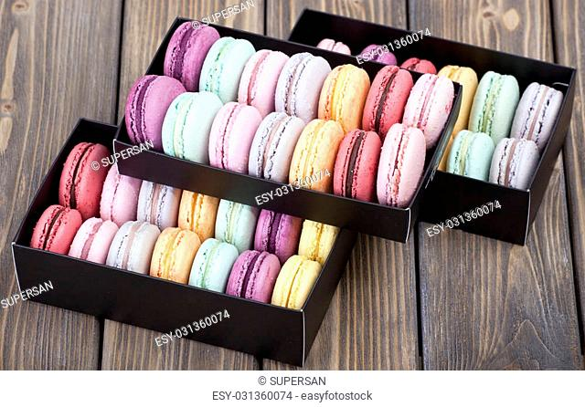 Colorful French Macaroon in black box on wooden background