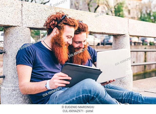 Young male hipster twins with red hair and beards sitting on bridge browsing digital tablet