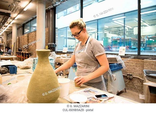 Woman in artist studio making pottery