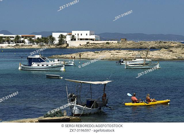 Els Pujols beach in Formentera with traditional fishing boat and kayaks in summer day. Llaüt boats