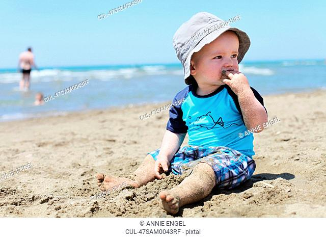 Toddler eating sand on beach