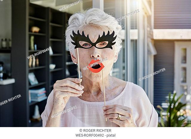 Senior woman hiding behind paper masks