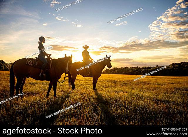 USA, Utah, Salem, Father and daughter (14-15) riding horses at sunset