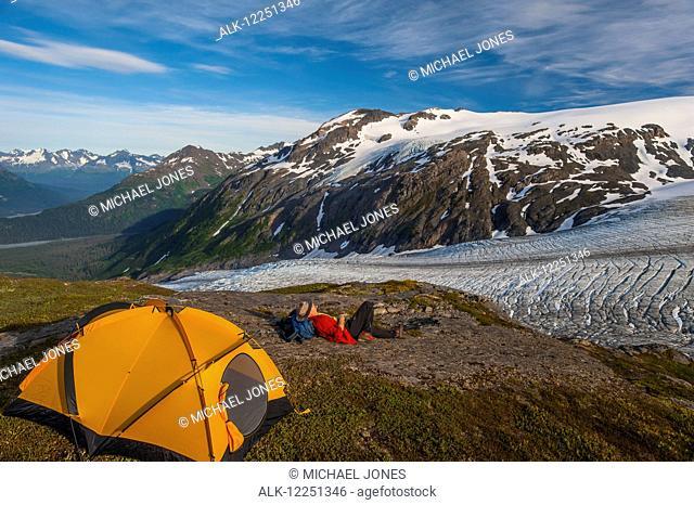 Backpacker at his campsite on a ridge overlooking Exit Glacier, Kenai Fjords National Park, Kenai Peninsula, Southcentral Alaska