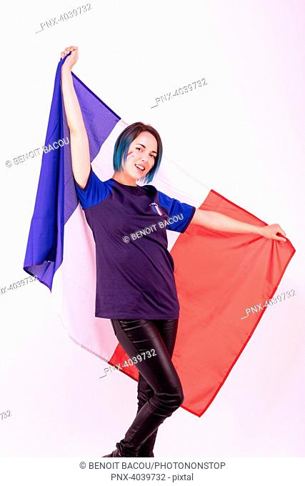 Portrait of a young supporter of the France football team, the national flag in her hands