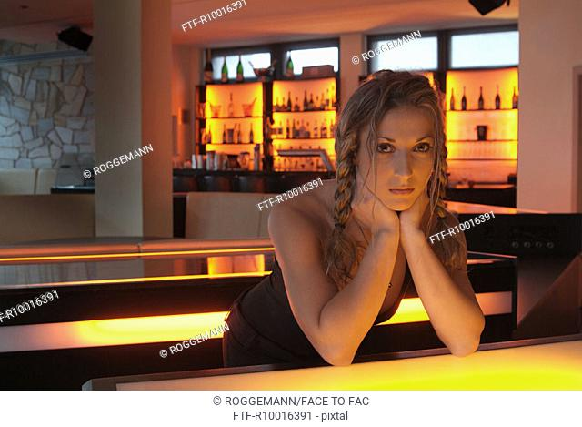 Woman with a plaits hairdo standing at the corner of a bar looks at the camera