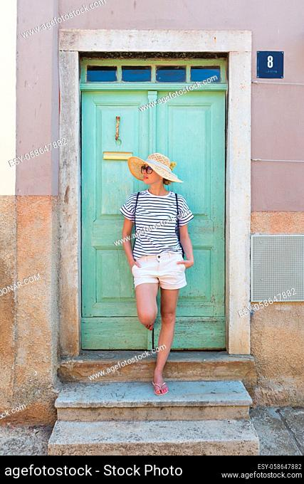 Beautiful young female tourist woman wearing sun hat, standing and relaxing in shade in front of turquoise vinatage wooden door in old Mediterranean town while...