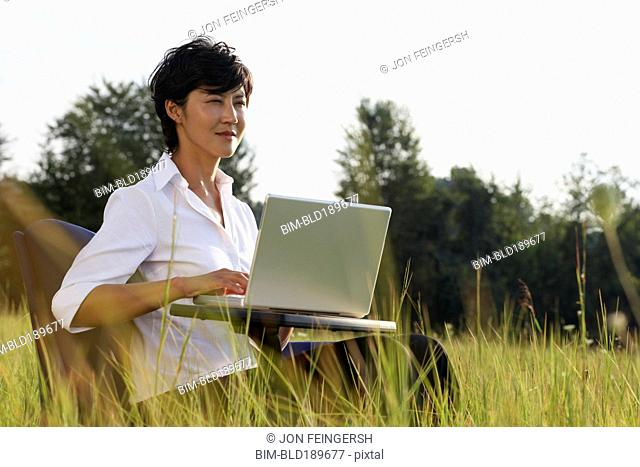 Asian businesswoman typing on laptop in field