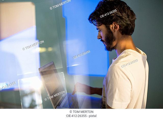 Casual businessman with laptop preparing audio visual presentation