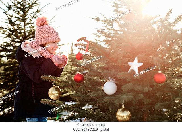 Girl looking at baubles on forest christmas tree