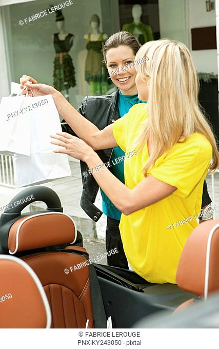Two women smiling near a car after shopping