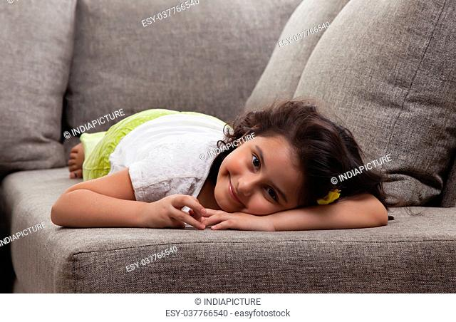 Little girl is relaxing on the sofa