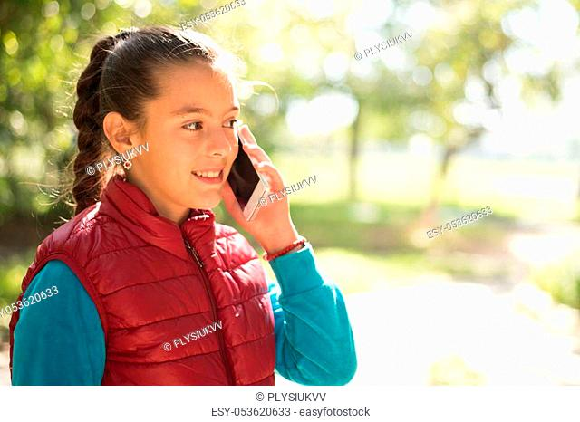 Beautiful girl talking on a smartphone in red vest on the outdoor. Handsome smiling girl with mobile phone walking on outdoor. Portrait smiles girl