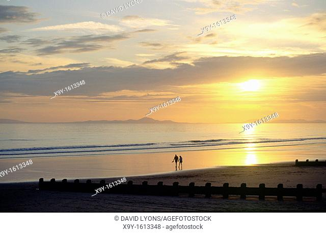 Sunset over the beach at the holiday seaside resort town of Barmouth in Gwynedd west Wales, UK  Young couple strolling on beach