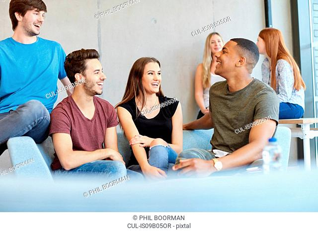 Group of young male and female students sitting on study space sofa chatting at higher education college