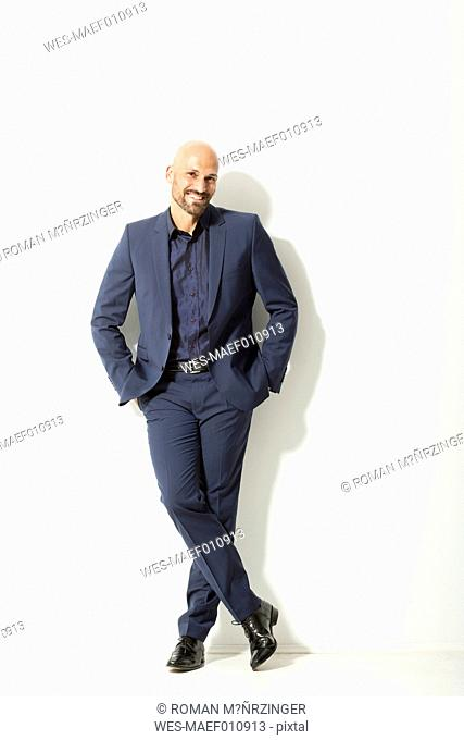 Portrait of bald man with beard wearing blue suit in front of white background