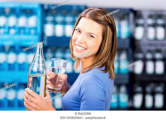 Smiling brunette woman holding water bottle and glass