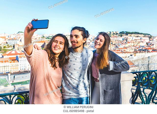 Three friends, outdoors, taking selfie with smartphone, Lisbon, Portugal
