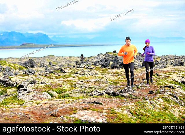 Exercise running sport. Runners on cross country trail run outdoors working out. Fit young fitness model man and asian woman training together outside in...
