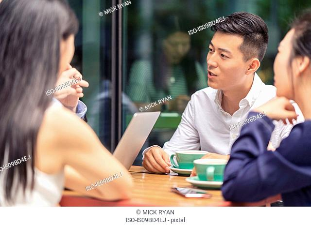 Group of businesspeople, having meeting at cafe, outdoors