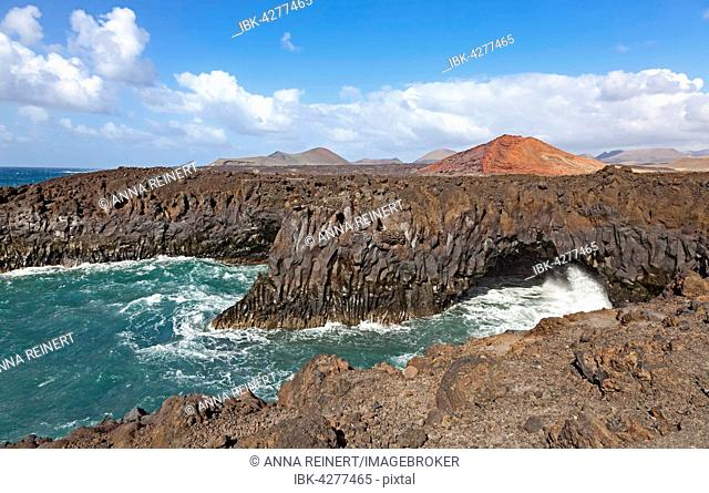 Rocky coast of Los Hervideros, volcanic landscape, Fire Mountains in Timanfaya National Park behind, Lanzarote, Canary Islands, Spain