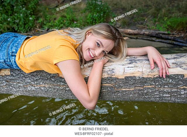 Smiling woman laying on a tree trunk at lakeshore
