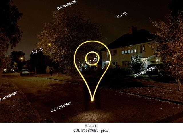 Light painted drop pin symbol floating on suburban street at night