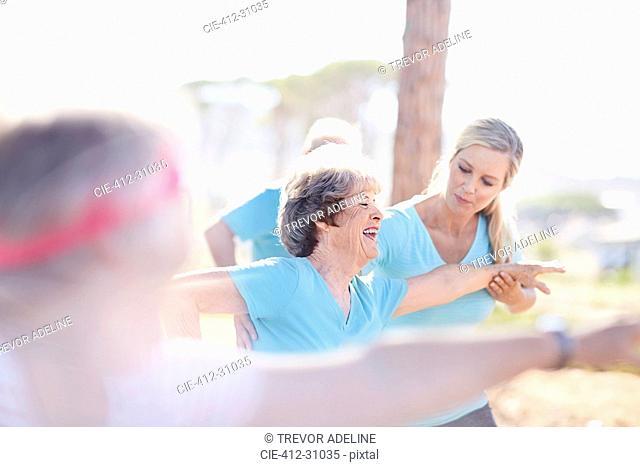 Yoga instructor guiding senior woman in sunny park