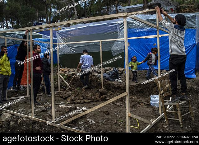 22 February 2020, Greece, Samos: Refugees build shelters from wooden beams. The Greek government is building a new camp for refugees on the island of Samos