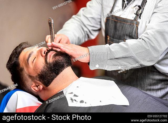 Handsome man having a shave with vintage razor at the barbershop