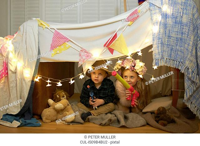 Girl and brother hiding in den with toy guns