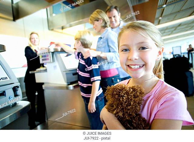 Family receiving ticket from female flight check-in attendant at airport check-in counter, focus on girl 7-9 holding soft toy in foreground, smiling, side view