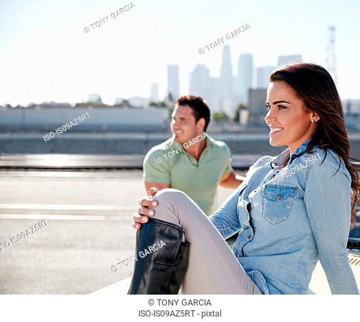 Couple by river looking away smiling