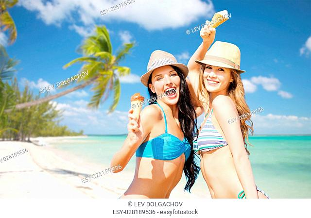 summer holidays, vacation, food, travel and people concept - smiling young women eating ice cream over exotic tropical beach with palm trees background