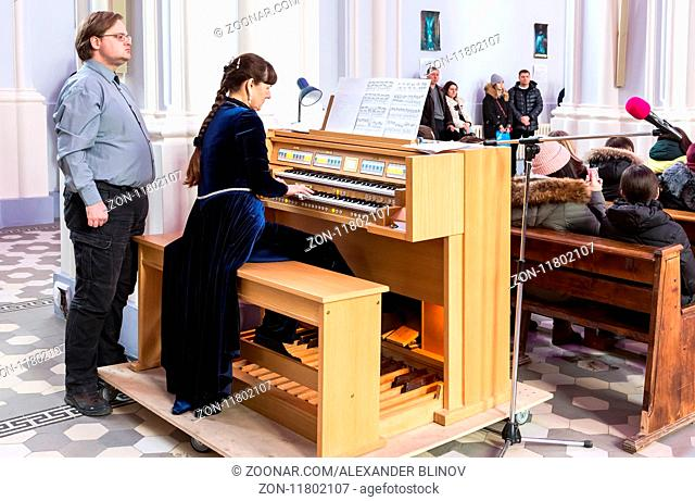 Samara, Russia - February 25, 2018: Woman playing on the electronic organ at the Roman Catholic parish of the sacred Heart of Jesus