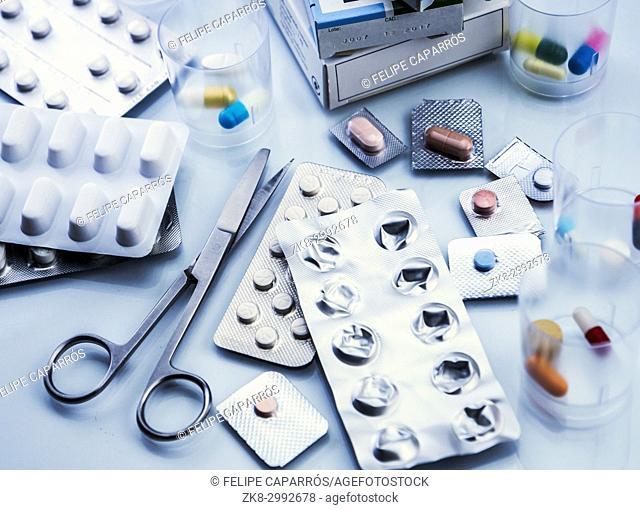 Scissors next to several blister cut, conceptual image