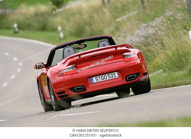 Porsche 911 Turbo Convertible, model year 2007-, red, driving, diagonal from the back, rear view, country road, open top