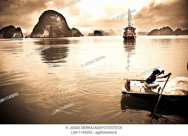 A young girl rows her boat on the waters of HALONG BAY, Vietnam