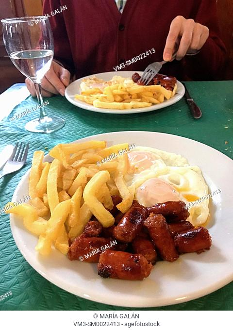 Fried eggs with chistorra and chips in a restaurant
