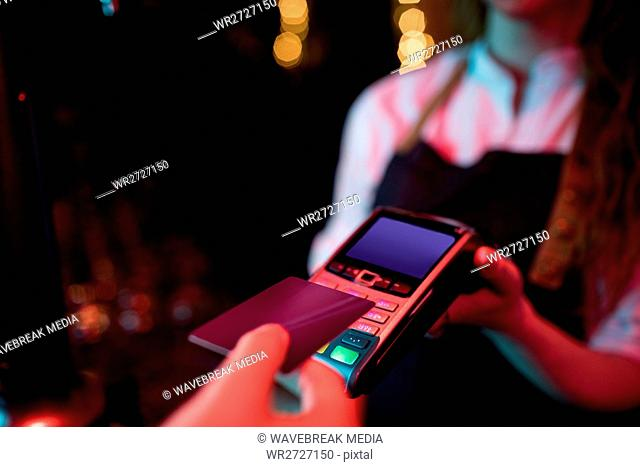 Customer making payment through credit card at counter