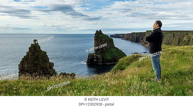 Man standing and looking out over the North Sea with rugged cliffs and sea stacks along the coastline; Scotland