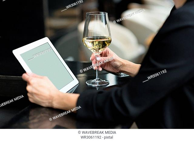 Businesswoman using a digital tablet and holding a champagne glass