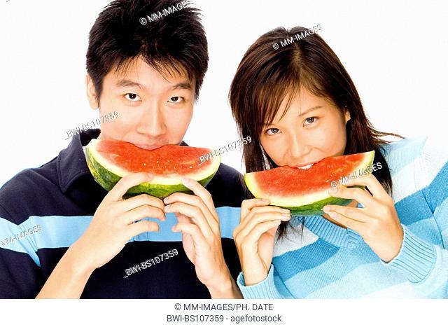 A young Asian couple enjoys tropical watermelon