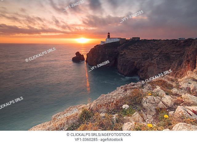 Sunset frames the lighthouse overlooking the Atlantic Ocean Cabo De Sao Vicente Sagres Algarve Portugal Europe