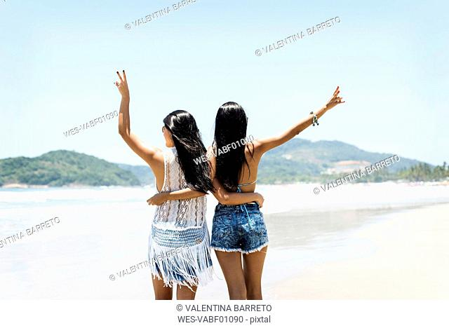 Brasil, Sao Paulo, Ubatuba, two young women standing arm in arm on the beach
