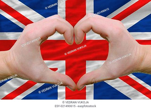 Heart and love gesture showed by hands over flag of uk backgroun