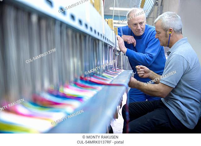 Workers using loom in textile mill