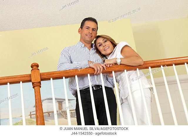 Smiling hispanic couple standing by railing in house